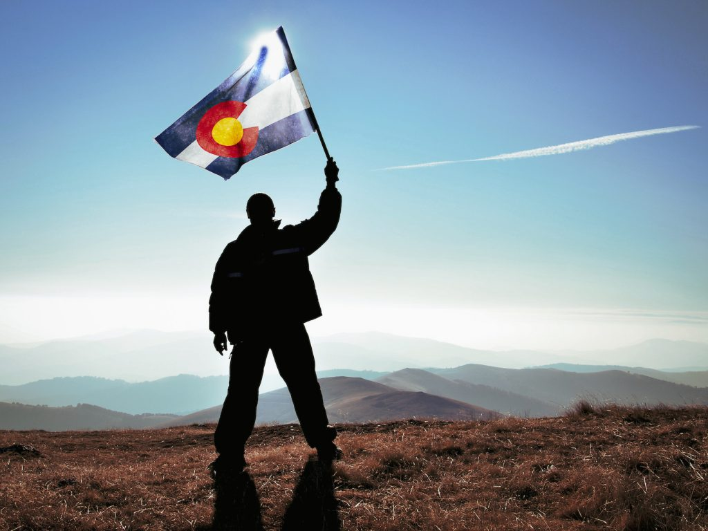 man stands on a plateau with Colorado flag raised