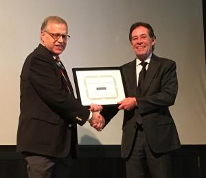 two men shake hands during an award presentation