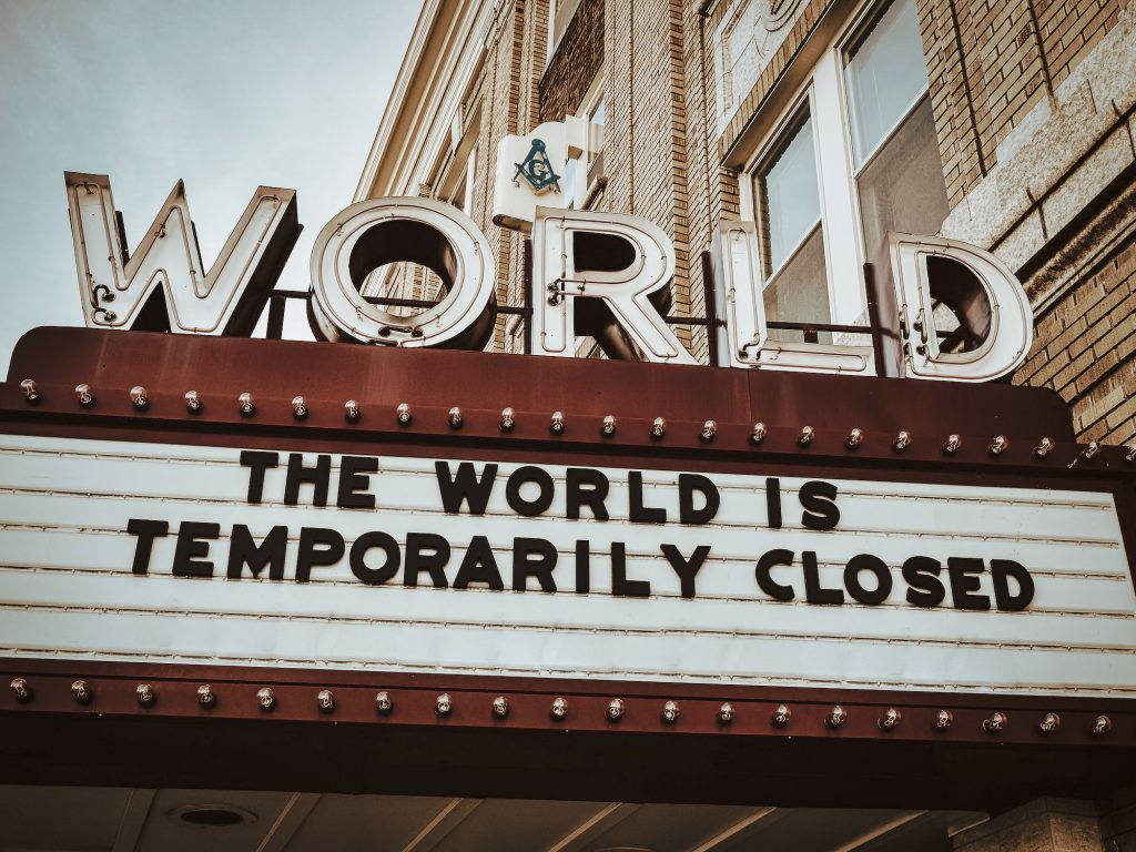 "marquee sign at world theater reading ""the world is temporarily closed"""
