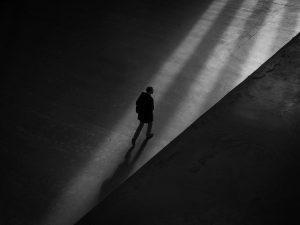 man walks through shadows on an empty street