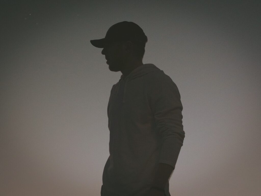 silhouette profile of a man in a baseball cap