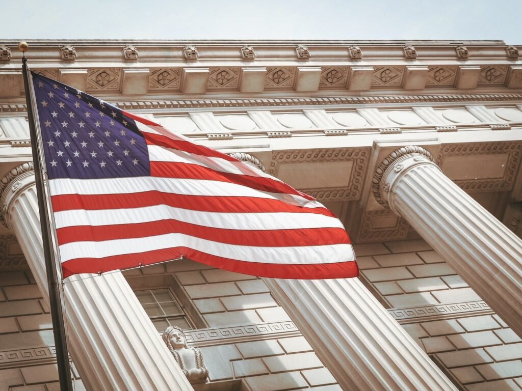 United States' flag flies in front of a large building with columns