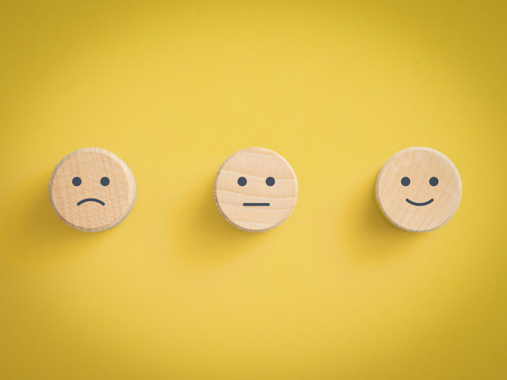 unhappy, neutral and happy icons against a yellow background